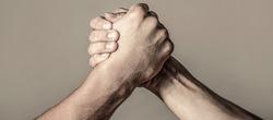 Arms wrestling. Closep up. Friendly handshake, friends greeting, teamwork, friendship. Handshake, arms, friendship. Hand rivalry vs challenge strength comparison. Man hand. Two men arm wrestling.