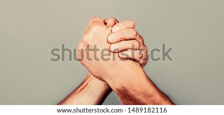 Arms wrestling. Friendly handshake, friends greeting, teamwork, friendship. Handshake, arms, friendship Man hand Two men arm wrestling