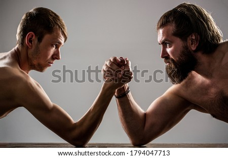 Arms wrestling thin hand, big strong arm in studio. Two man's hands clasped arm wrestling, strong and weak, unequal match. Heavily muscled bearded man arm wrestling a puny weak man.