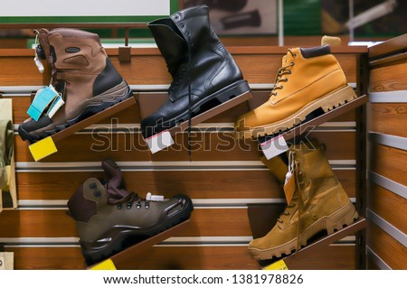 Army boots stand in line at the store counter. Fishing shoes about hunting in the store