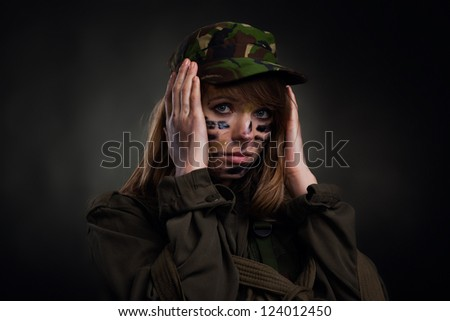 army girl cover ears with hands, soldier woman in a military uniform over black background