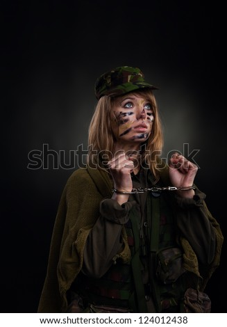army girl in handcuffs, soldier woman in a military uniform over black background