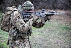 Army infantry, special forces fighter, commando shooter in camouflage uniform, beanie, carrying backpack, aiming service rifle, shooting on enemy in autumn forest, observing area with collimator sight