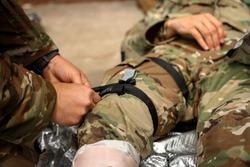 Army medics practicing tourniquet application