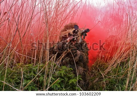 Army sniper with a background of red smoke