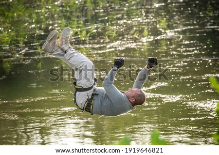 Army soldier conducts the rope bridge water crossing exercise. Water survival training Foto d'archivio ©