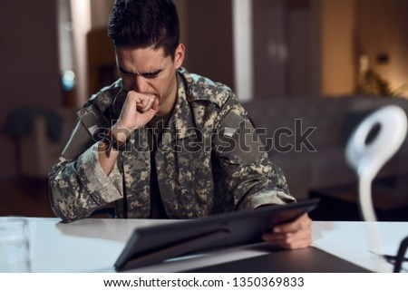 Army soldier experiencing emotional pain while holding framed picture and feeling homesick.