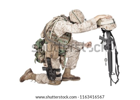 Army soldier in sorrow for fallen comrade, standing on knee, leaning on rifle with helmet and two dog tags on chain, studio shoot isolated on white. Military funeral honors, grief for killed in action