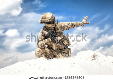 Army soldier or airsoft player in camo uniform and helmet, armed assault rifle, standing on knee on sand dune, looking back and showing halt or stop hand signal. Nonverbal communication on battlefield
