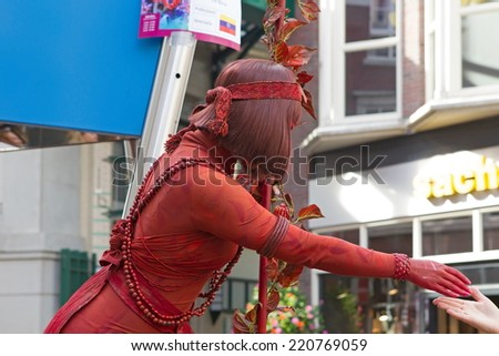 Arnhem, Netherlands - September 28, 2014: artist lady in red during world championships living statues in Arnhem