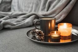 Aroma candles of orange color, coffee in a black mug and decorative pine cones served on a metal tray. Autumn or winter atmosphere