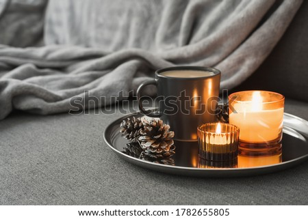 Photo of  Aroma candles of orange color, coffee in a black mug and decorative pine cones served on a metal tray. Autumn or winter atmosphere