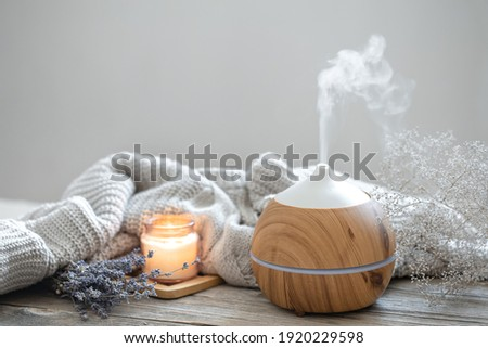 Aroma composition with a modern aroma oil diffuser on a wooden surface with a knitted element, candle and lavender. Stock foto ©
