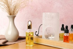 Aroma lamp and essential oils on wooden table