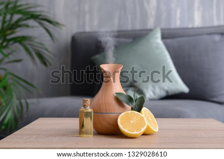 Aroma oil diffuser and citrus fruit on table in room Stock foto ©