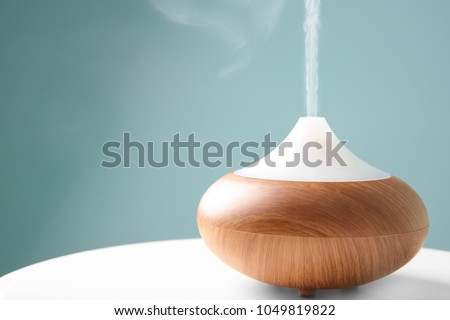 Aroma oil diffuser on table against color background