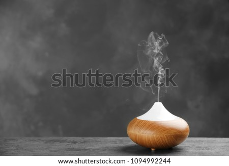 Aroma oil diffuser on table against grey background. Air freshener