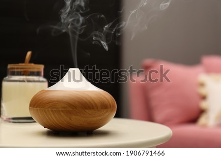Aroma oil diffuser on table in room. Space for text Stock foto ©