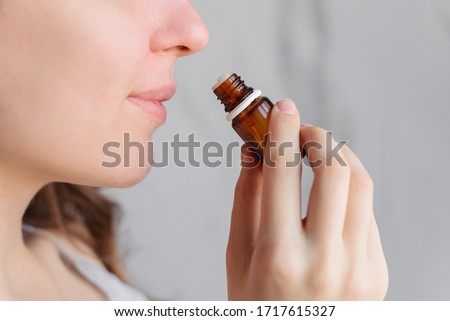 Aromatherapy: a girl with beautiful skin holds a bottle of essential oil near her nose and inhales. Close up, bright marble background.