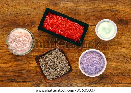 Aromatherapy and hygiene bath product selection of scented crystal bath salts with natural lavender seeds and facial care cosmetic cream in jars and bowls on wood table in wellness and relaxation spa