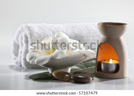 Aromatherapy candle and frangipani flower