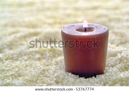 Aromatherapy candle burning on a bed of natural bath sea salts in a spa