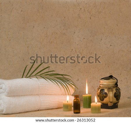 aromatherapy candles and oil with bath towels at spa
