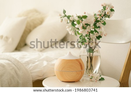 Aromatherapy Concept. Aroma oil diffuser on chair against in the bedroom. Air freshener. Ultrasonic aroma diffuser for home Foto stock ©