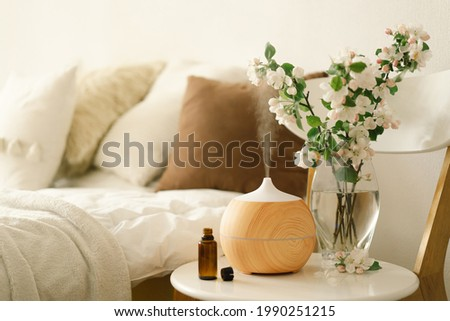 Aromatherapy Concept. Aroma oil diffuser on chair against in the bedroom. Air freshener. Ultrasonic aroma diffuser for home Stock foto ©
