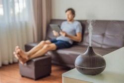 Aromatherapy Concept. Wooden Electric Ultrasonic Essential Oil Aroma Diffuser and Humidifier. Ultrasonic aroma diffuser for home. Man resting at home