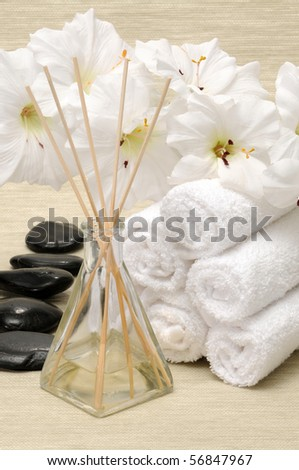 Aromatherapy diffuser, towel, rocks and flower in a spa