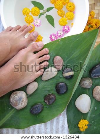 Aromatherapy foot massage treatment using warm pebbles.