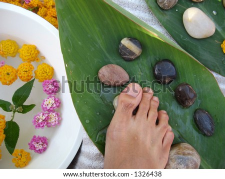 Aromatherapy foot massage treatment using warm pebbles.