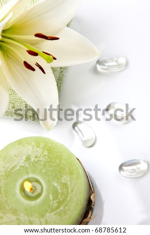 Aromatherapy lily spa set -  lily flowers, aroma candle, spa stones and and towels over white background best suited for relaxing and health commercials