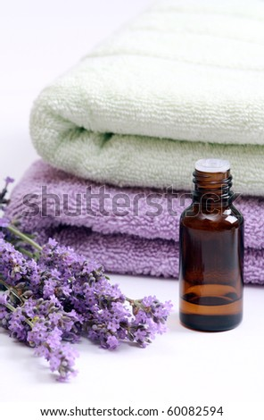 Aromatherapy oil and lavender flowers against terry towels