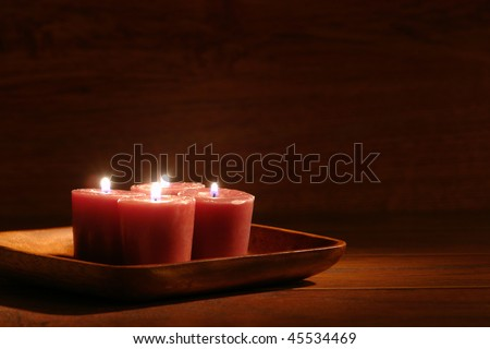 Aromatherapy organic natural candles burning in a wood dish in a spa