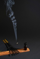 Aromatherapy, relaxation and yoga. Smoke from aroma sticks moves on a black background