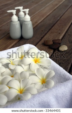 Aromatherapy spa objects - Fragrant Frangipani, lotions and pebbles.