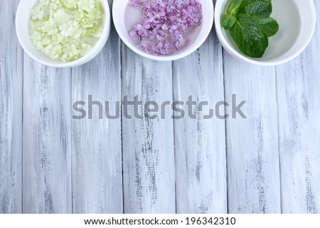 Aromatherapy treatment bowls with flowers and perfumed water on wooden background