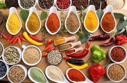 Aromatic and colorful spices in ceramic containers on a wooden background.