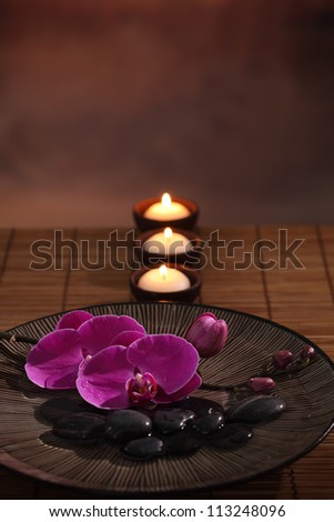 Aromatic candles and orchid flower in bowl,zen concept.