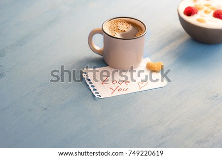 "Aromatic coffee and ""love you"" message - Mug of Arabic coffee and a heart-shaped sugar on a math paper with the love you message and a bowl of yogurt on a blue wooden table, in the morning light. #749220619"