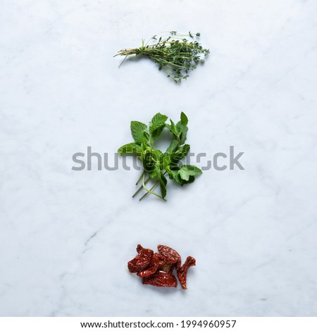 Aromatic Flavoring, Isolated on Marble Background – Dried Tomatoes from Italy, Bunch of Thyme Twigs, Mint Bundled with Twine on Stone Kitchen Table – Detailed Close-Up Macro, High Resolution, Top View Stock photo ©