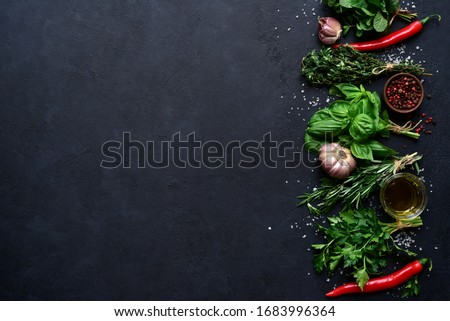 Aromatic fresh herbs and spices on a black slate, stone or concrete background. Top view with copy space.