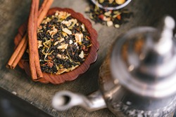 Aromatic fruity black tea dried leaves and cinnamon bark strips laid on small wooden tray with metal kettle in foreground