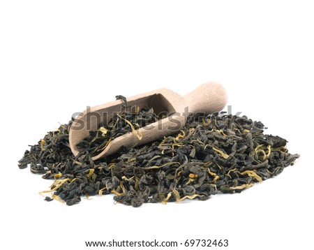 Aromatic green tea leaves with marigold petals and wooden shovel on white background