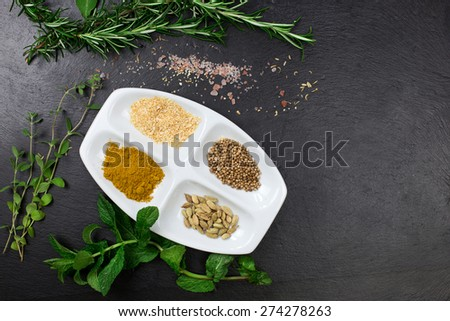 aromatic herbs and dried spices over slate sheet