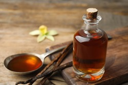 Aromatic homemade vanilla extract on wooden table, closeup. Space for text