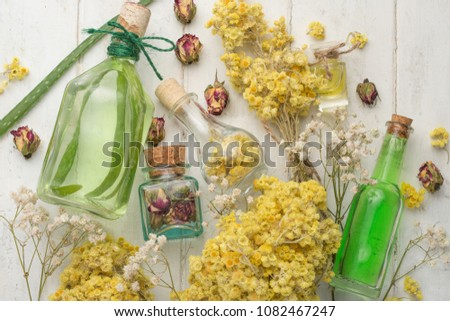 Aromatic oil, aromatic herbs in glass bottles, on a wooden background. The concept of body care and beauty #1082467247