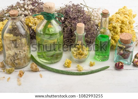 Aromatic oil, aromatic herbs in glass bottles, on a wooden background. The concept of body care and beauty #1082993255